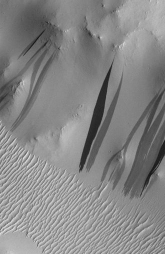 Dark slope streak - Dark slope streaks in Arabia Terra as seen by Mars Orbital Camera (MOC) on Mars Global Surveyor spacecraft. The darkest streaks are only about 10% darker than their surroundings. The greater apparent contrast in the image is due to contrast enhancement Image is 1.65 km (1 mi) across. North is at bottom.