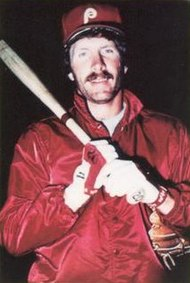 Portrait of Phillies' third baseman Mike Schmidt looking at the camera and holding a bat across his chest