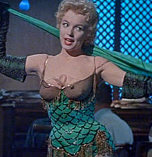 Monroe in Bus Stop. She is wearing a green stage costume with gold trimmings while singing.