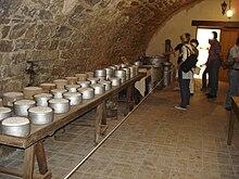 La photographie couleur représente une cave voutée en pierre. Une longue table en bois sur des tréteaux porte des fromages frais dans des moules métalliques et en terre cuite. Au fond de la salle, des visiteurs examinent des ustensiles en aluminium: bidons de lait et marmites de grand volume.