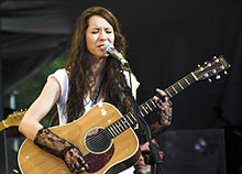 A woman is on stage singing into a mic and playing a guitar.