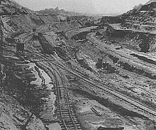 Image showing an excavation being cut into hills with crisscrossed railway tracks.