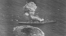 Aerial view of a cloud of smoke rising from a battleship at sea