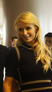 Smiling blonde woman in dark clothing