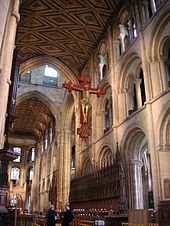 This interior view of Peterborough  shows part of the very long nave and the chancel with no screen dividing the building. The structure is mostly of a unified Norman appearance with three levels of simple round-topped arches, only the tall arches of the central tower being Gothic. Other visible features are the ancient painted ceiling, the medieval choir stalls and the modern Rood which has a gilt wooden figure of Christ on a red cross, suspended high in front of the tower arch.