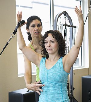 Pilates - Pilates teacher using verbal and tactile feedback to ensure proper form