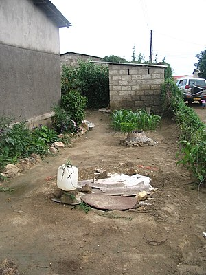 Pit latrine - Common problem: water well (forefront) is in close proximity to the pit latrine (brick building at the back), leading to groundwater pollution (example from Lusaka, Zambia)