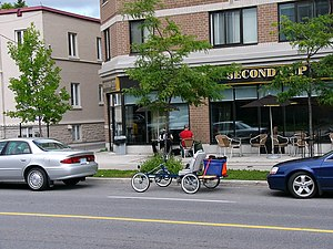 Car-free movement - A quadracycle parked on a Canadian urban street amongst the cars