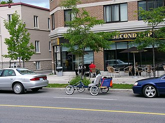 Quadracycle - A Rhoades Car 4W2P '4-wheel bike' parked on a Canadian urban street amongst the cars.