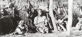Os homens sentam-se contra a parede, claramente cansados.  Alguns estão dormindo.
