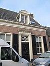 foto van Eenvoudig woonhuis zonder verdieping en met zadeldak, waarin dakvenster met gebogen fronton