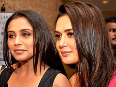 Rani Mukerji and Preity Zinta stand beside one another, and face away from the camera