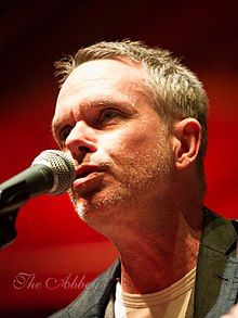 Rick Price cantando en un micrófono con un fondo rojo oscuro