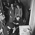 Rode kruis medewerkster controleert de hand van een oudere man, Bestanddeelnr 900-4661.jpg