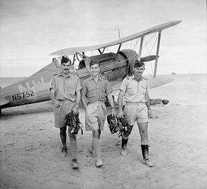 Three men in khaki shirts and shorts with forage caps, in front of a biplane