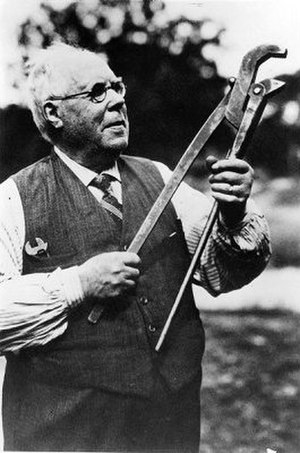 Johan Petter Johansson - J. P. Johansson with his favourite tool and invention, the plumber wrench. In his breast pocket, an adjustable spanner, also invented by him.