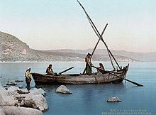 photograph of fishermen in a simple boat on the lake, close to the rocky shore