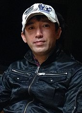A photograph of a Japanese man wearing a baseball cap.
