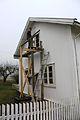 Snekker setter inn nytt vindu på et stillasje av tre 3.JPG