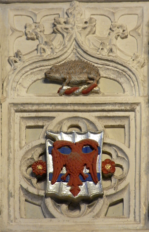 """John Speke (1442-1518) - Decorated panel within Speke Chantry, Exeter Cathedral, showing on a spiked escutcheon à bouche the arms of Sir John Speke: Argent, two bars azure over all an eagle displayed with two heads gules; with canting crest (on a torse): A porcupine proper (French: porc-é(s)pic, (""""spiky-pig""""))"""