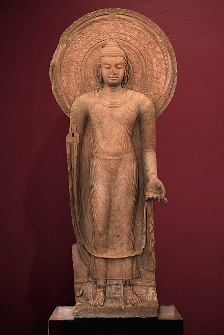 Standing Buddha in red sandstone, Mathura, Gupta art, circa 5th century CE. Mathura Museum. Standing Buddha Installed by Buddist Monk Yasadinna - Circa 5th Century CE - Jamalpur Mound - ACCN 00-A-5 - Government Museum Mathura Red background.jpg