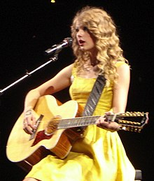 Taylor Swift performing with a guitar in a yellow dress