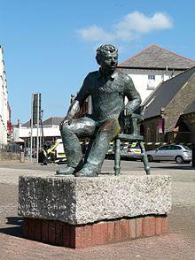 Uma estátua de bronze de Thomas no Bairro Marítimo, Swansea