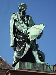 statue en bronze de gutenberg par david dangers 1840 place gutenberg strasbourg la houppelande releve sur la jambe gauche et le bonnet bord de - Johannes Gutenberg Lebenslauf