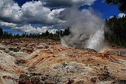 Água e vapor saindo de um solo rochoso e árido.  Abetos em segundo plano.