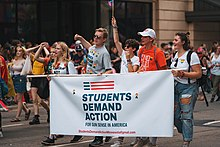 "Five young adults march holding a banner that reads ""Students Demand Action for Gun Sense in America"". In the background, other people march and look on as the parade they are marching in passes by."