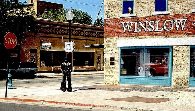 "The ""Take It Easy"" statue created by Ron Adamson of Libby, Montana and mural at 35deg1'24.54"" N, 110deg41'53.02"" W at Second St. & Kinsley Ave. in Winslow, Arizona TakeItEasy WinslowAZ.jpg"