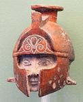 Terracotta a forma di testa con elmo, da tomba a Lagos T380, 600-575 ac. ca.JPG