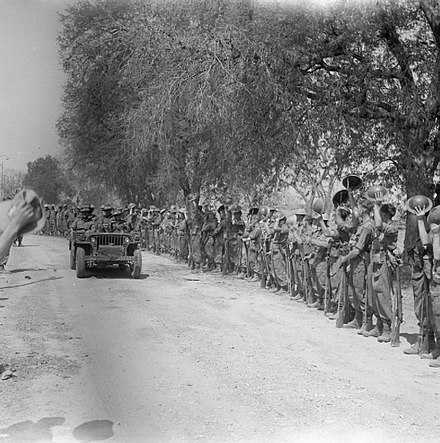 Lieutenant General Sir William Slim and Major General T. W. Rees are cheered by troops as they leave Mandalay in a jeep, March 1945. The British Army in Burma 1945 SE3530.jpg