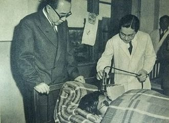 Daigo Fukuryū Maru - Medical professionals, before the era of whole body counting, assessing the activity of a bedridden crew member by using a geiger counter on 31 March 1954, focusing on the person's hair which would have collected dusty fallout.