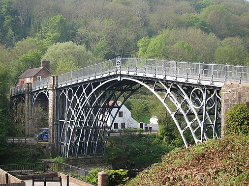 The application of the steam engine allowed coke to be substituted for charcoal in iron making, lowering the cost of iron, which provided engineers with a new material for building bridges. This bridge was made of cast iron, which was soon displaced by less brittle wrought iron as a structural material The world's first iron bridge.jpg