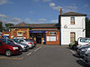 "A brown-bricked building with a rectangular, dark blue sign reading ""THEYDON BOIS STATION"" in white letters all under a blue sky with white clouds"