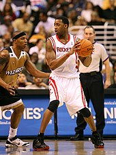 "A basketball player, wearing a white jersey inscribed with the word ""ROCKETS"" across the front, holds a basketball away from another basketball player guarding him. A referee stands in the background."