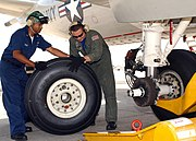 Two man replace a main landing gear tire of a plane