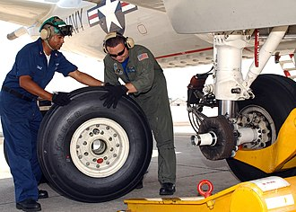 Two mechanics replacing a main landing gear wheel on a Lockheed P-3 Orion Two man replace a main landing gear tire of a plane.jpg