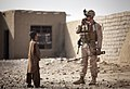 U.S. Marine Capt. Owen Boyce, the commanding officer of Headquarters and Service Company, 3rd Battalion, 3rd Marine Regiment, relays a message on his radio as an Afghan boy looks on during a compound search in 120401-M-MM918-006.jpg