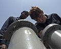 U.S. Navy Chief Cryptologic Technician (Technical) Winston Wright, left, supervises as Cryptologic Technician (Technical) Seaman Apprentice Christopher McCutcheon loads anti-ship missile defense chaff rounds 140629-N-PJ969-096.jpg