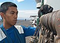 US Navy 030604-N-1512S-028 Airman Charles Imanil from Dededo, Guam, places a chain on the chock and chain holder on the flight deck aboard USS Kearsarge (LHD 3).jpg