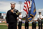 US Navy 050314-N-3271W-005 Journalist 1st Class Andrew Scharnhorst assigned to Navy Recruiting District Phoenix, sings God Bless America, while a Naval Junior Reserve Officer Training Corps (NJROTC) color guard from Independenc