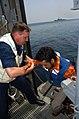 US Navy 050512-N-9446C-012 Senior Chief Boatswain's Mate Gary Arehart, assists a Motor Vessel Olympias crew member aboard the Nimitz-class aircraft carrier USS Carl Vinson (CVN 70).jpg