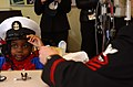 US Navy 060220-N-5330L-018 Chief Fire Controlman Jeff H. Mullins, stationed aboard the guided-missile destroyer USS McFaul (DDG 74), lends his cover to a patient to try on.jpg
