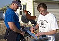 US Navy 071031-N-3750S-043 Lt. Cmdr. Bradley Slocum, and Chief Yeoman Nora Lundberg, attached to the Navy Operational Support Center San Antonio, cut pieces of wood for the porch of a Habitat for Humanity project house.jpg