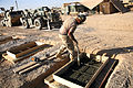 US Navy 071107-M-4804L-017 A Seabee assigned to Naval Mobile Construction Battalion (NMCB) 15, mixes setting concrete while building structures for the different units in the Al Anbar province of Iraq.jpg