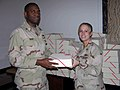 US Navy 071221-N-4521B-001 Chief Yeoman Anthony Darby, left, hands a holiday gift box to Legalman 1st Class Carole McCoy.jpg