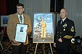 US Navy 090108-N-7656T-076 Artist Thomas Stahl presents Command Master Chief Jon Port with a portrait of former President George H.W. Bush as a young naval aviator.jpg