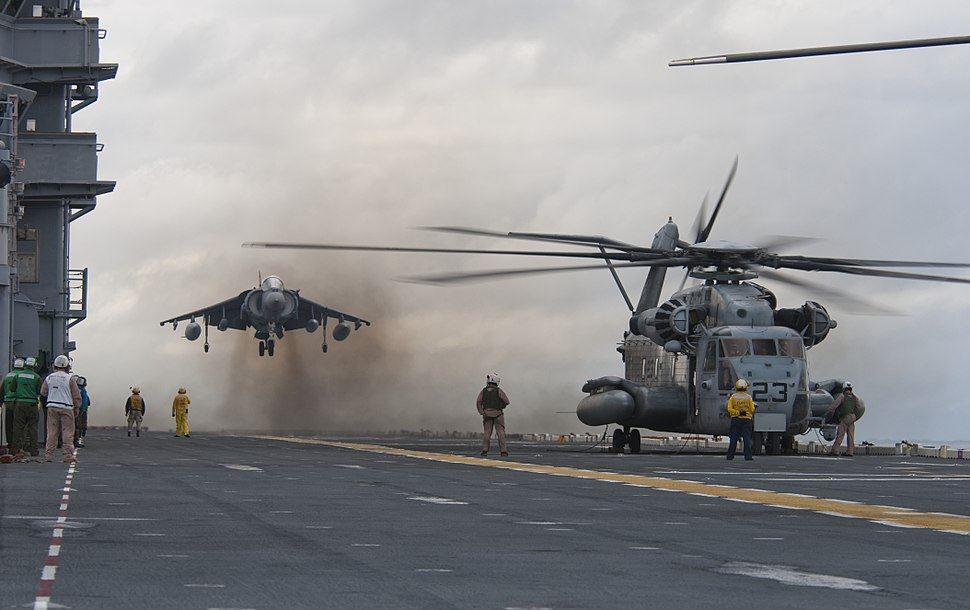 US Navy 091026-N-5319A-025 An AV-8 Harrier from Marine Attack Squadron (VMA) 223 lands next to an MH-53E Sea Dragon helicopter aboard the amphibious assault ship USS Nassau (LHA 4) during flight operations